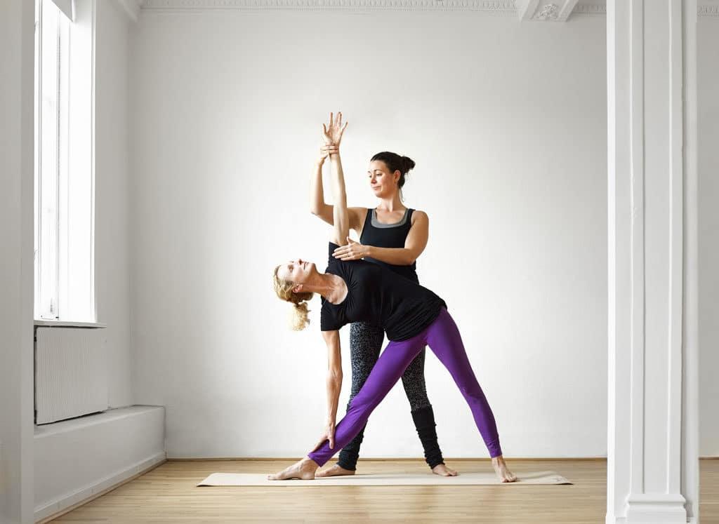 En personer i Yoga Position 1c blir korrigerad av yogalärare